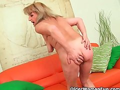 Grandmother near large breasts pushes huge dildo inside