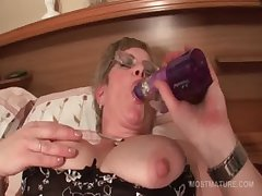 Mature in glasses fucks herself anent big dildo