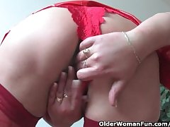 Mature mom in deviating outfit rubs her clit and toys her pussy